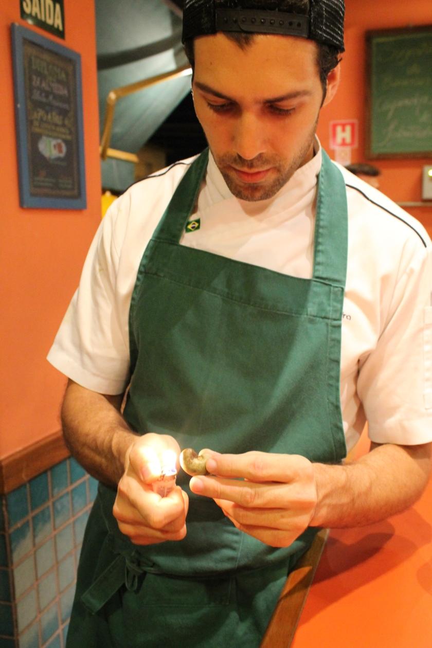 Rodrigo Oliveira vom Mocotó versucht eine Cashew-Nuss zu öffnen